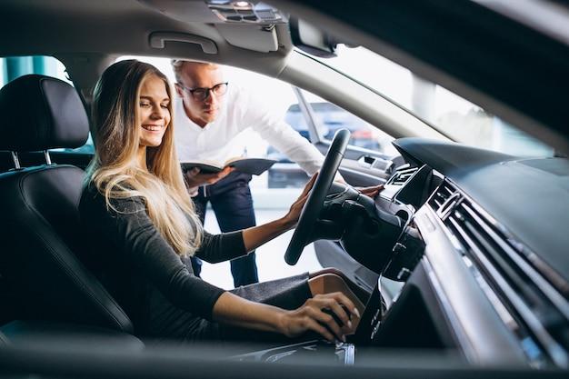 Молодая женщина тестирует автомобиль из автосалона