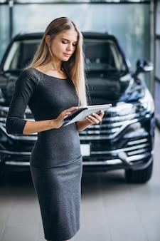 Женщина продавец в автосалоне на машине