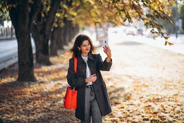 Молодая женщина, с помощью телефона в осенний парк