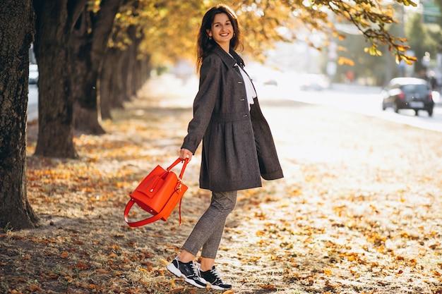 秋の公園で歩いている若い女性