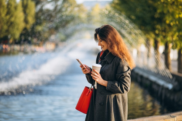 Молодая женщина пьет кофе и использует телефон в парке