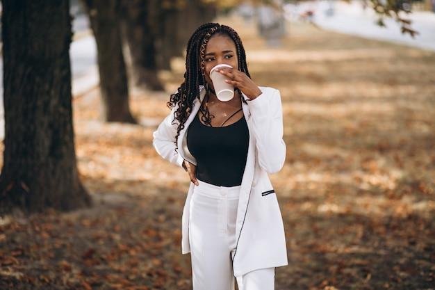 公園で白いスーツに身を包んだ若いアフリカ人女性