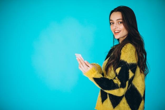 電話を使用して暖かいセーターの若い女性