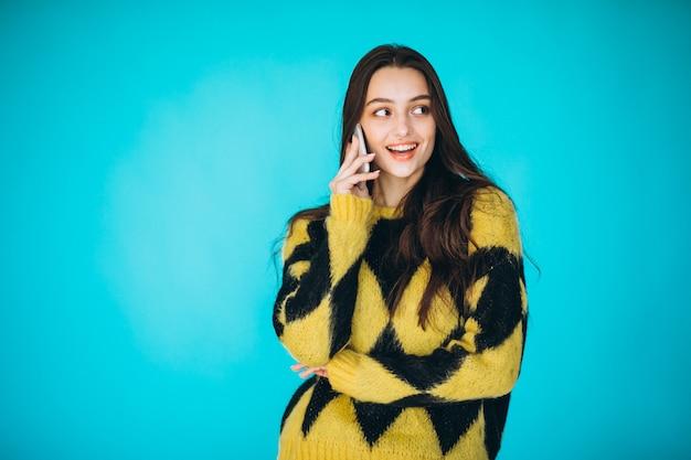 Молодая женщина в теплый свитер с помощью телефона
