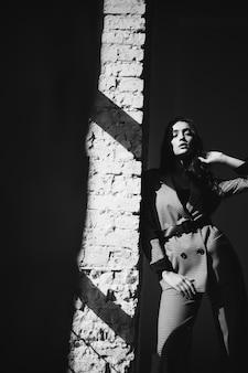 レンガの壁でビジネススーツの女性