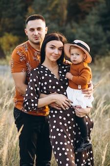 秋の畑で小さな娘と家族