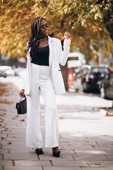 通りの外の白いスーツに身を包んだ若い女性