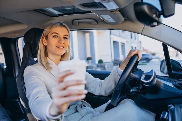 Женщина сидит внутри электро автомобиля во время зарядки с чашкой кофе