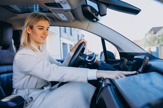 Женщина сидит внутри электро автомобиля во время зарядки