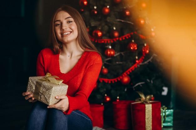 Женщина сидит у елки и распаковывает подарок на рождество