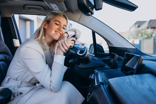 充電しながら電気自動車の中に座っている女性
