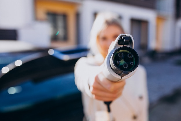Женщина заряжает электро автомобиль у ее дома и держит зарядное устройство