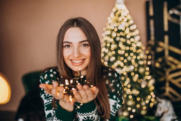 クリスマスの白熱灯とクリスマスツリーで若い女性