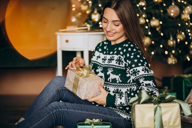 Молодая женщина распаковывает подарок на елку