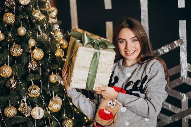 クリスマスツリーでクリスマスプレゼントを開梱する若い女性