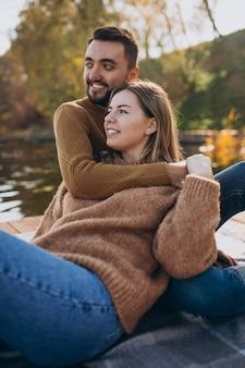 川沿いのデッキブリッジに座っている若いカップル