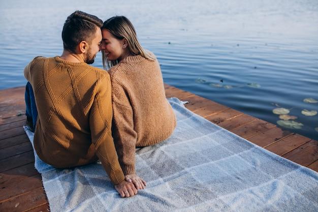 Молодая пара сидит на палубном мосту у реки