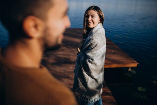Счастливая пара с одеялом у реки