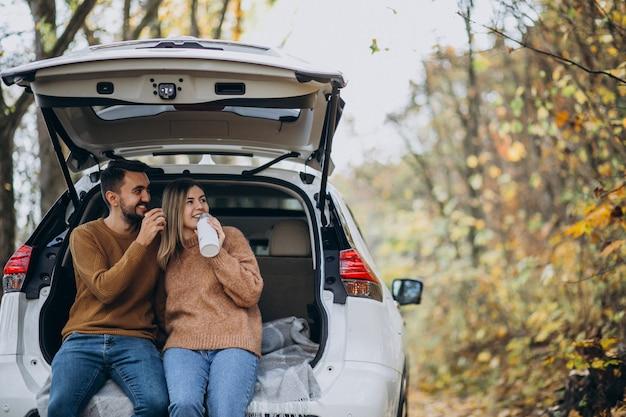 森でお茶を飲む車の後ろに座っている若いカップル