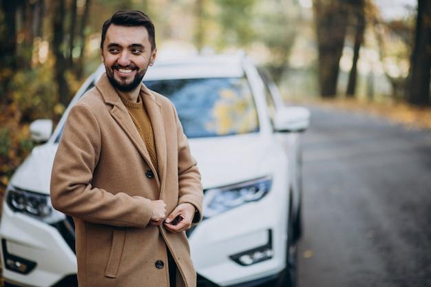 車でコートを着ている森の若い男