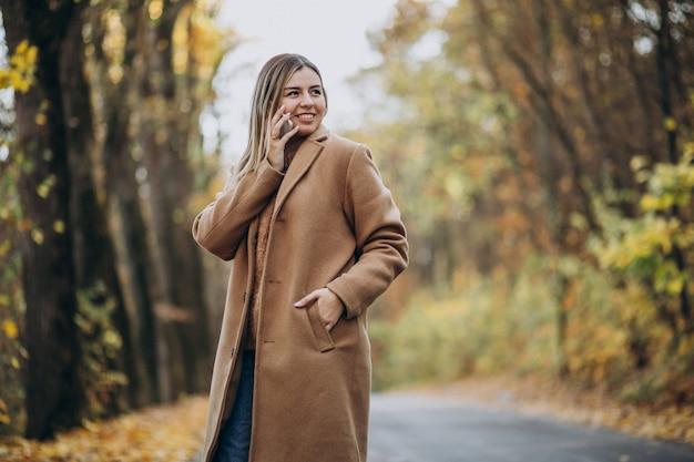 秋の公園で道に立っているコートの若い女性