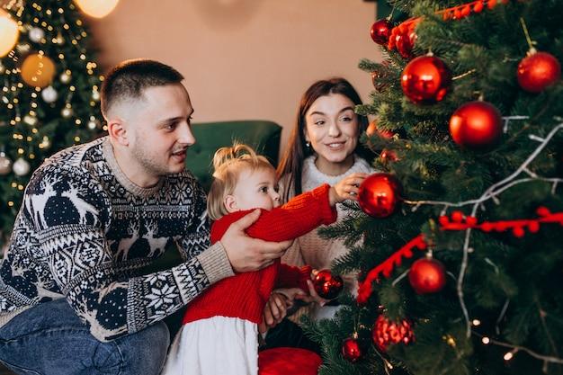 クリスマスツリーにおもちゃをぶら下げ小さな娘と家族