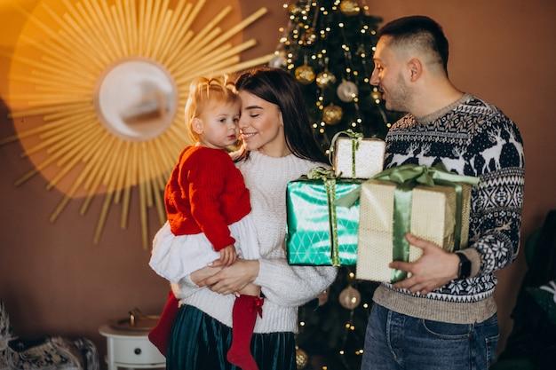 Семья с маленькой дочкой у елки распаковывает подарочную коробку
