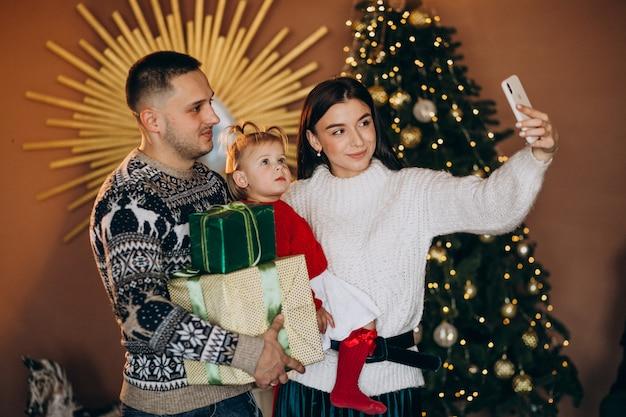 ギフト用の箱を開梱するクリスマスツリーで小さな娘と家族