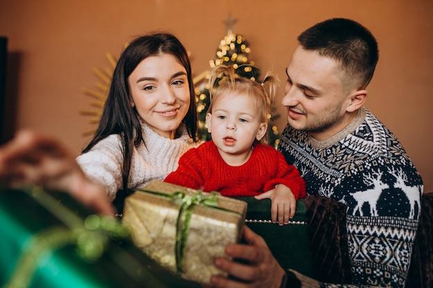 Семья с маленькой дочерью сидит возле елки и распаковывает подарочную коробку