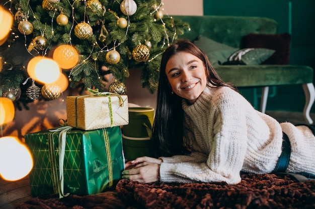 クリスマスツリーの贈り物を開梱して若い女性