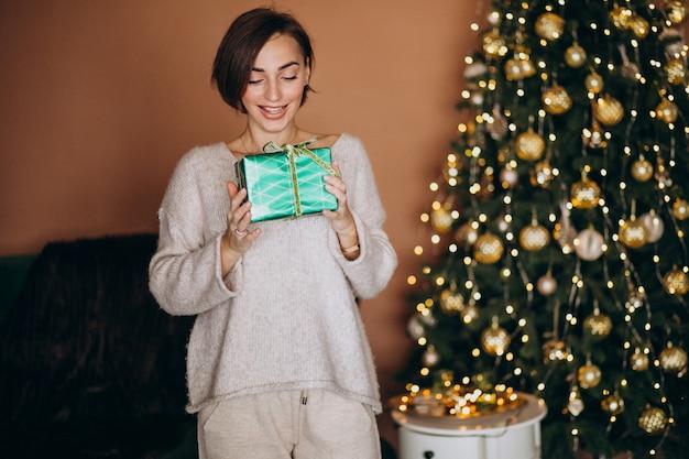 Молодая женщина с рождественским подарком у елки