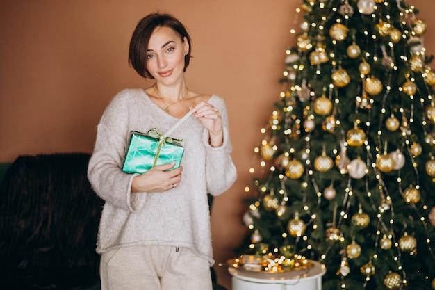 クリスマスツリーがクリスマスプレゼントを持つ若い女性