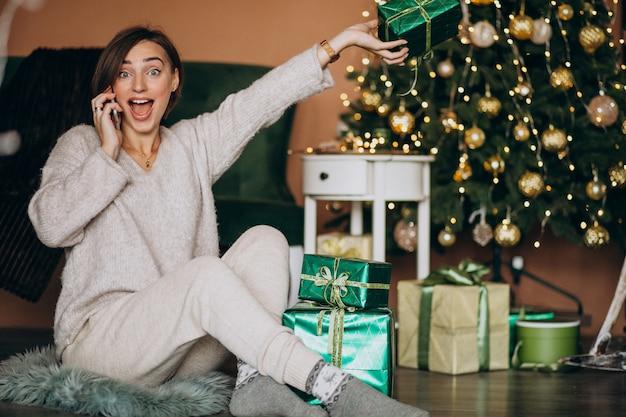 Женщина сидит у елки и делает покупки по телефону