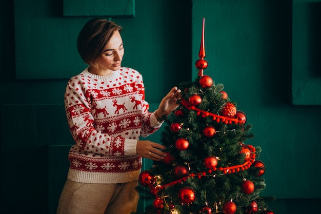 赤いおもちゃでクリスマスツリーを飾る女性