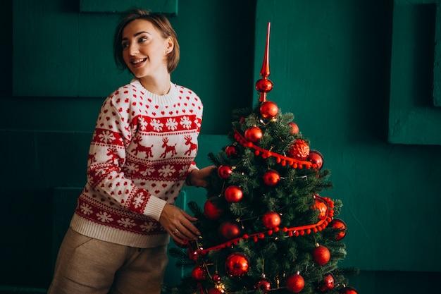 Женщина украшает елку красными игрушками
