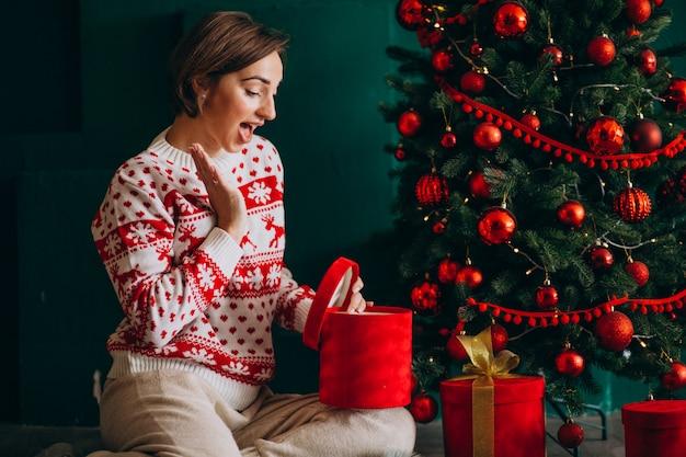 Молодая женщина, сидя у елки с красными коробками