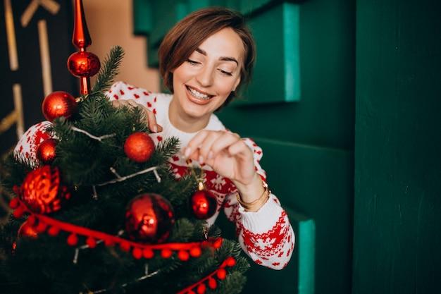 赤いボールでクリスマスツリーを飾る女性