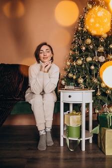 Счастливая женщина, сидя на диване у елки