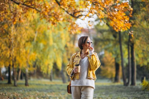 コーヒーを飲みながら秋の公園で若い女性