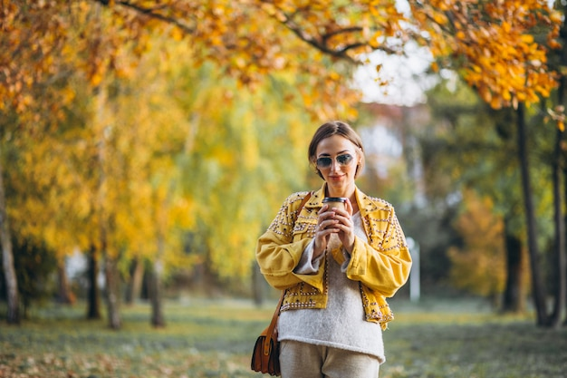 Молодая женщина в осеннем парке, пить кофе