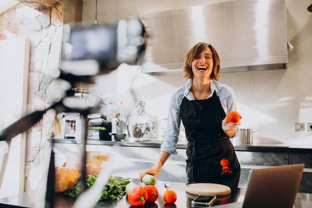 若い女性のビデオブロガー、キッチンで料理と撮影