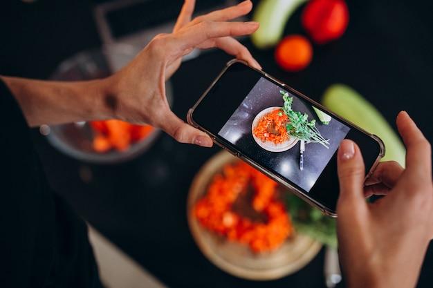 彼女の携帯電話で食事の写真を作る女性
