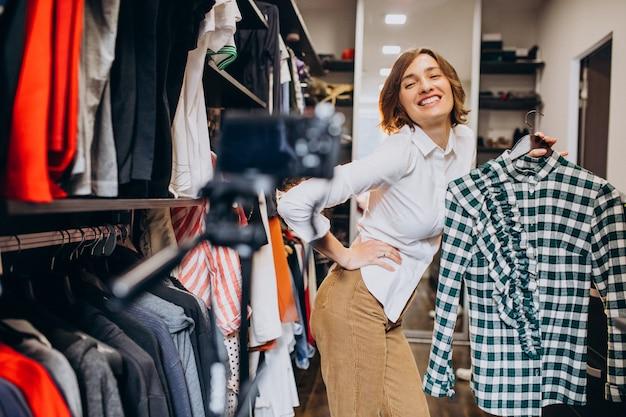 自宅の女性が彼女のチェックルームから布を選ぶ