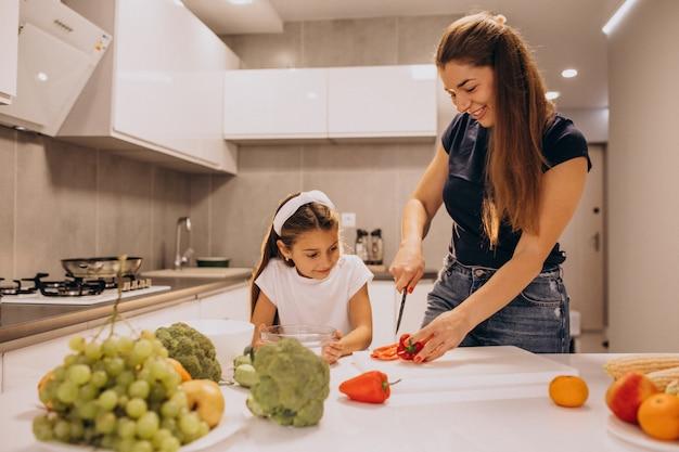 台所で料理を一緒に小さな娘を持つ母