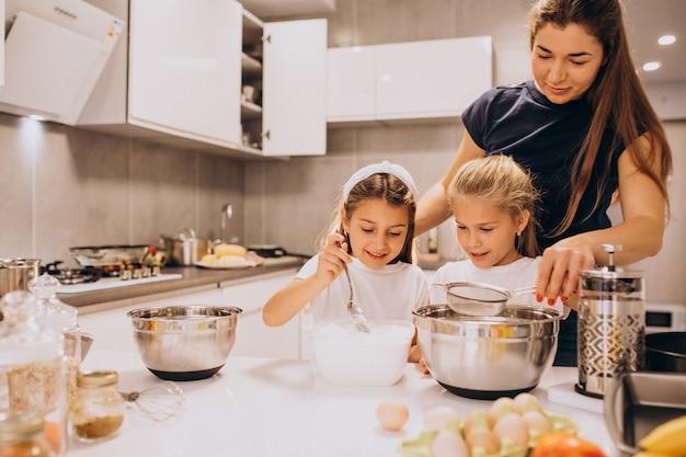 Мать с двумя дочерьми на кухне выпечки