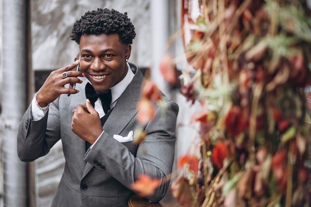 Молодой африканский бизнесмен используя телефон