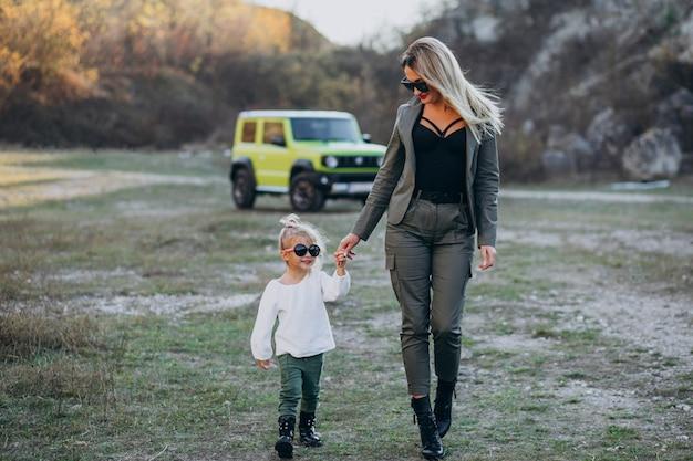 車で公園で小さなかわいい娘を持つ若い母親