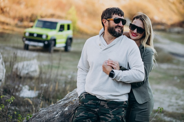 車で旅行する若いカップルは、公園で散歩を停止