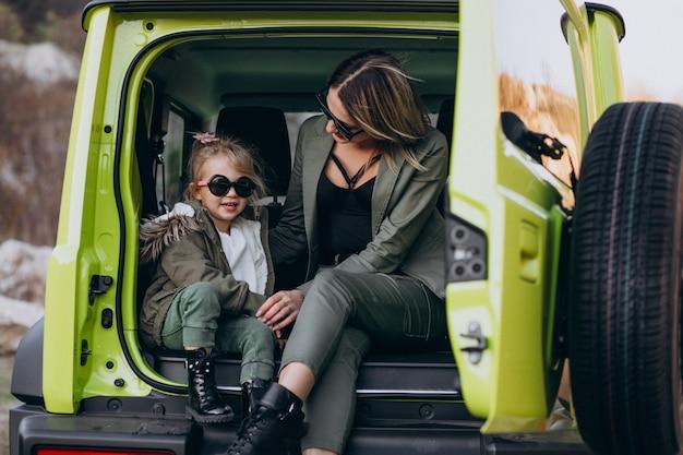 Мать с маленькой дочкой сидит в задней части машины