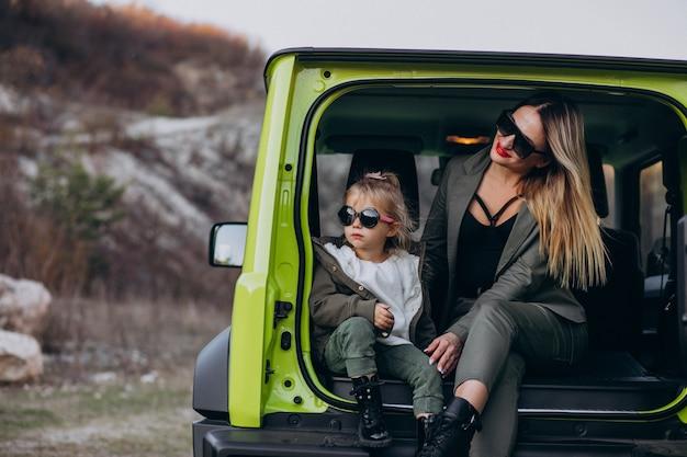 車の後ろに座っている彼女の小さな娘を持つ母
